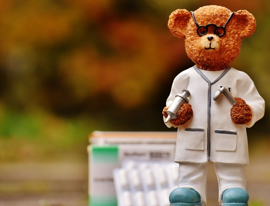 Small ceramic bear in doctors outfit in front of boxes of tablets