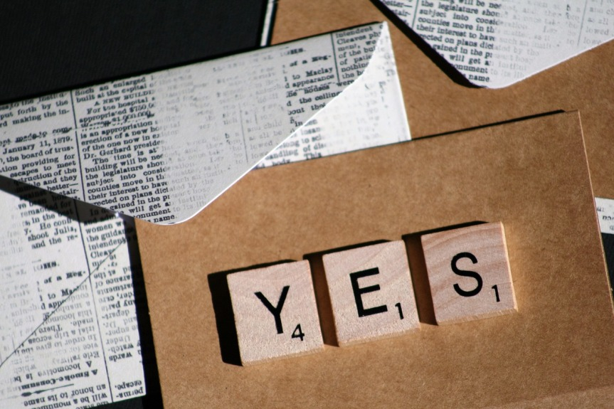 Brown card with YES in wooden Scrabble letters