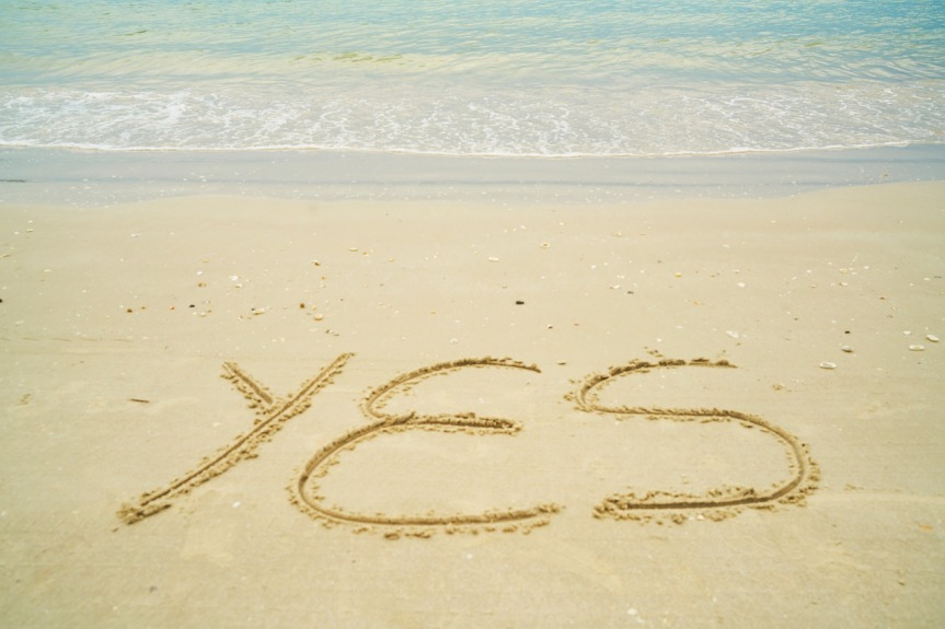 YES written in sand on a beach.