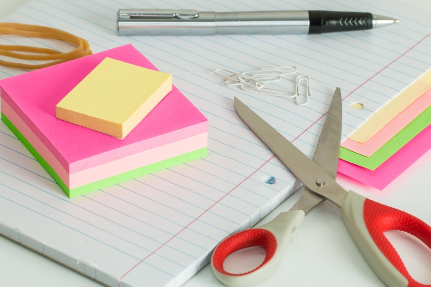 stationary pile with scissors, a notebook, a pen and sticky notes.