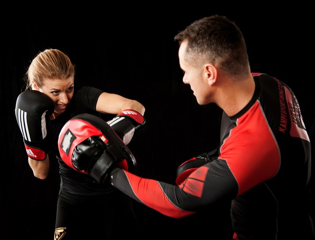 Woman and man in boxing gear fighting