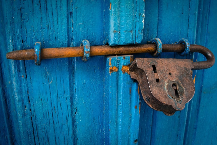 Blue wooden door with a metal bolt and lock