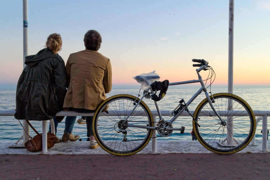 Two people with backs to the camera looking out at a sunset seated on a metal barrier next to a road bike.
